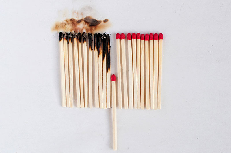 Matches in a row and a single match out of alignment, having the left matches burnt and the single match preventing a burnout