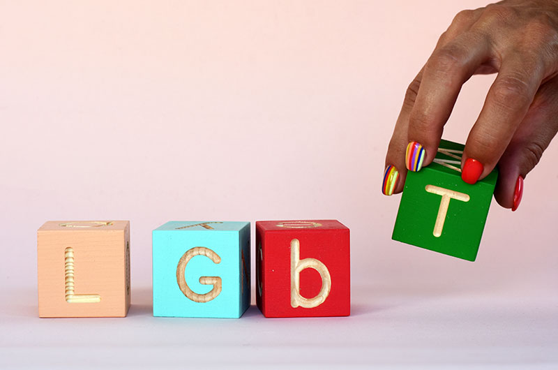 Four different colored blocks, each with a letter, with colors that represent LGBTQ+