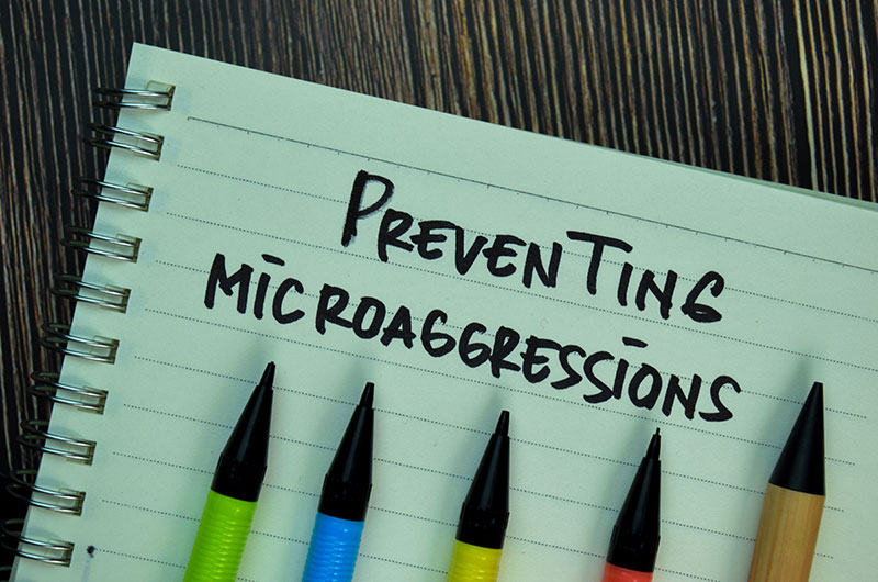 Notebook page with five different colored pens with the words preventing microaggressions written on the notebook page