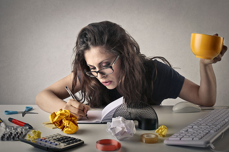 Woman sitting at a desk appearing either productive or busy with office items on the desk and several crumbled papers