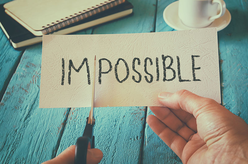 Paper with the word impossible written on it, with an individual holding scissors about to cut the paper