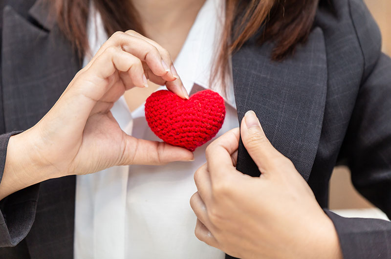 Woman wearing business clothing with a cloth heart held by her hand towards her heart