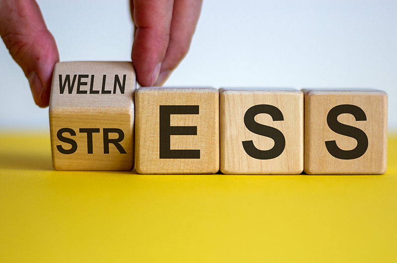 Four wooden blocks with the first block tiled to reveal the blocks spelling out two words, wellness and stress