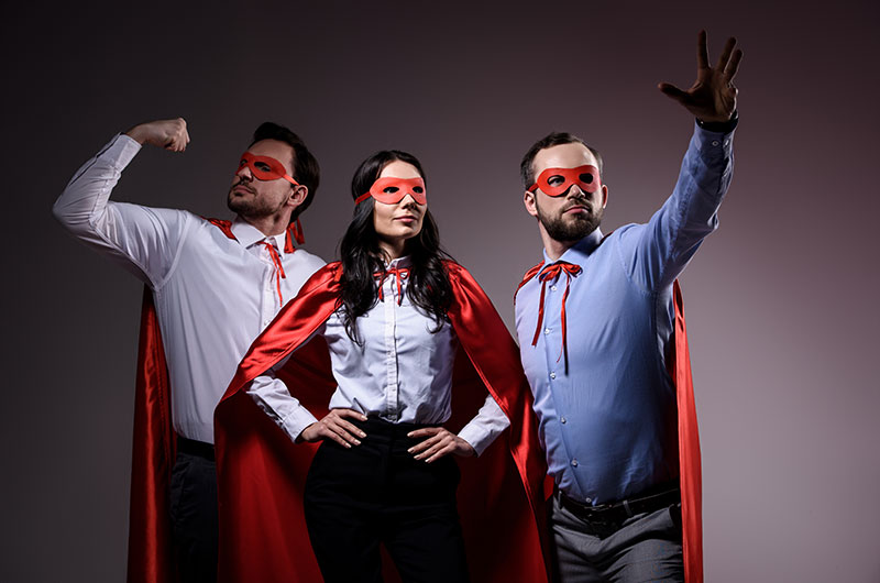 Three adults posing as superheroes, wearing red superhero attire with business clothes underneath
