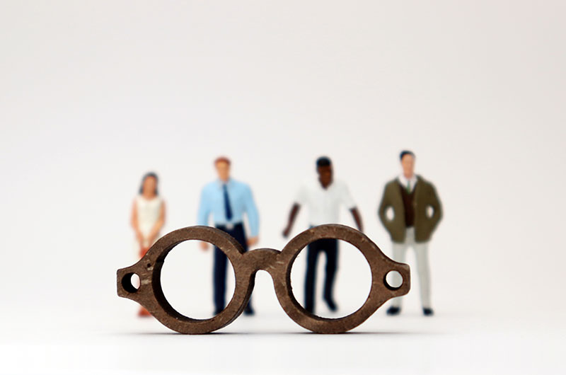 Metal glasses with no frames, with four individuals in the background that are blurred, representing unconscious bias
