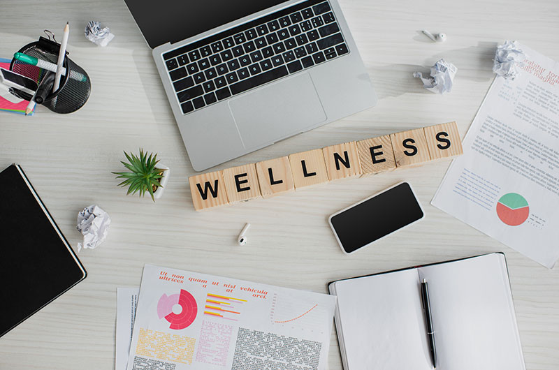 Scrabble pieces on a desk, surrounded by office items, that spell out the word wellness
