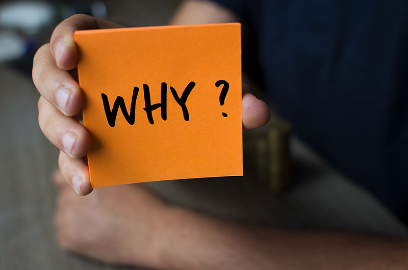 Individual holding up an orange postit with the word why and a question mark