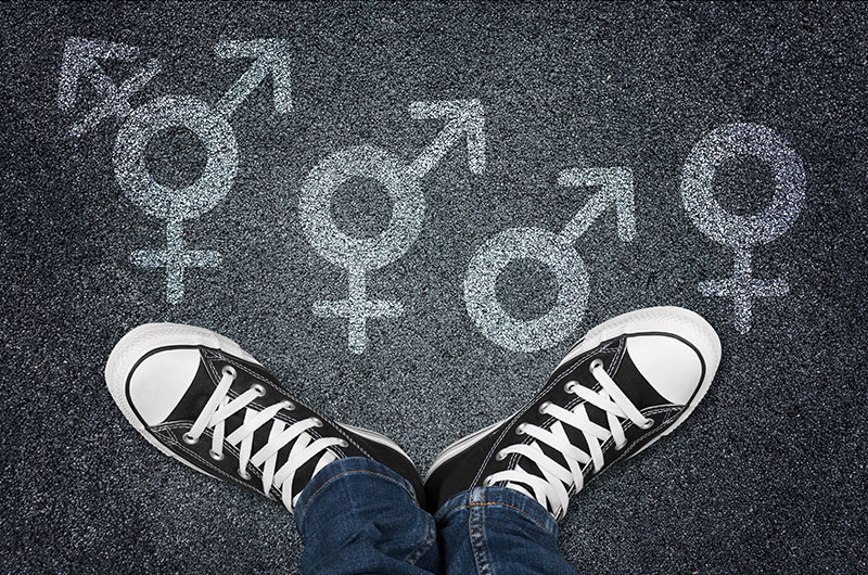 Pavement with chalk in shapes of different genders, with an individual's feet standing on the pavement