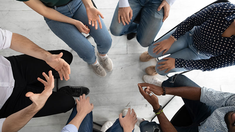 Group of diverse individuals sitting in a circle, on chairs, having a group counseling session