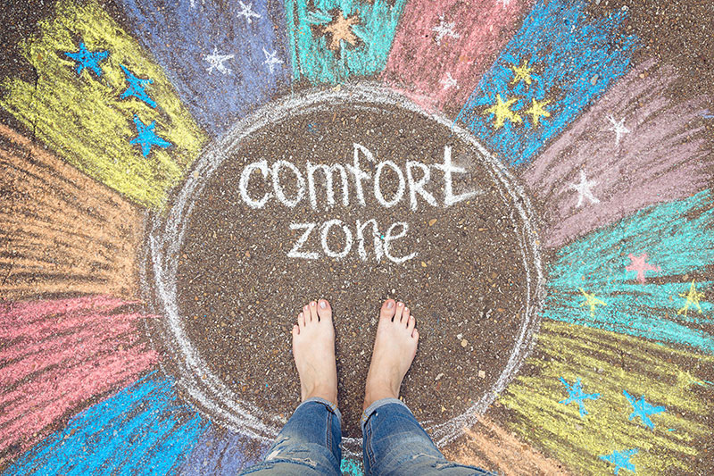 Chalk of different colors, on pavement, with an individual's feet standing inside a circle with the words comfort zone